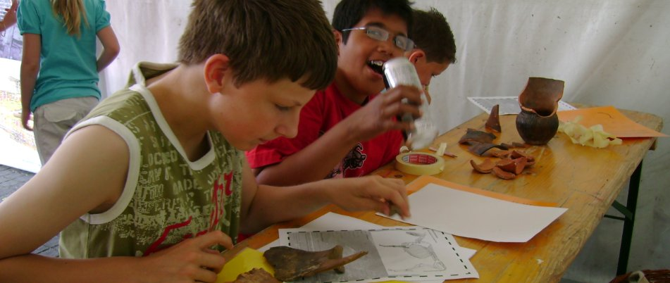 children studying archaeological finds